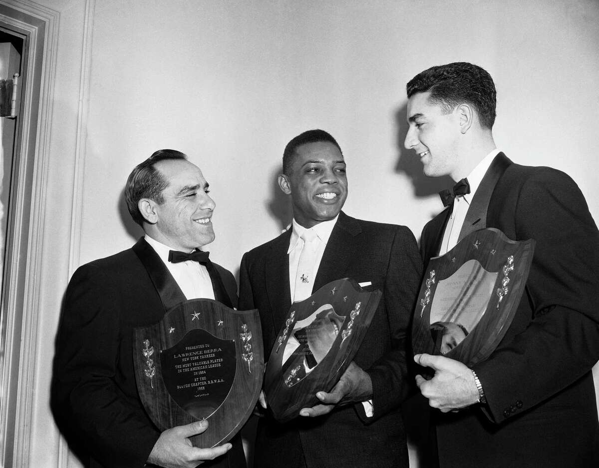 Yankee catcher Yogi Berra, left, and New York Giants center fielder Willie Mays, center and Hurley Johnny Antonelli hold plaques after being honored by the Boston Baseball writers in Boston on Jan. 26, 1955. Yogi and Willie were honored as the most valuable players in their respective leagues while Antonelli was singled out as the Giants' ace mounds man.