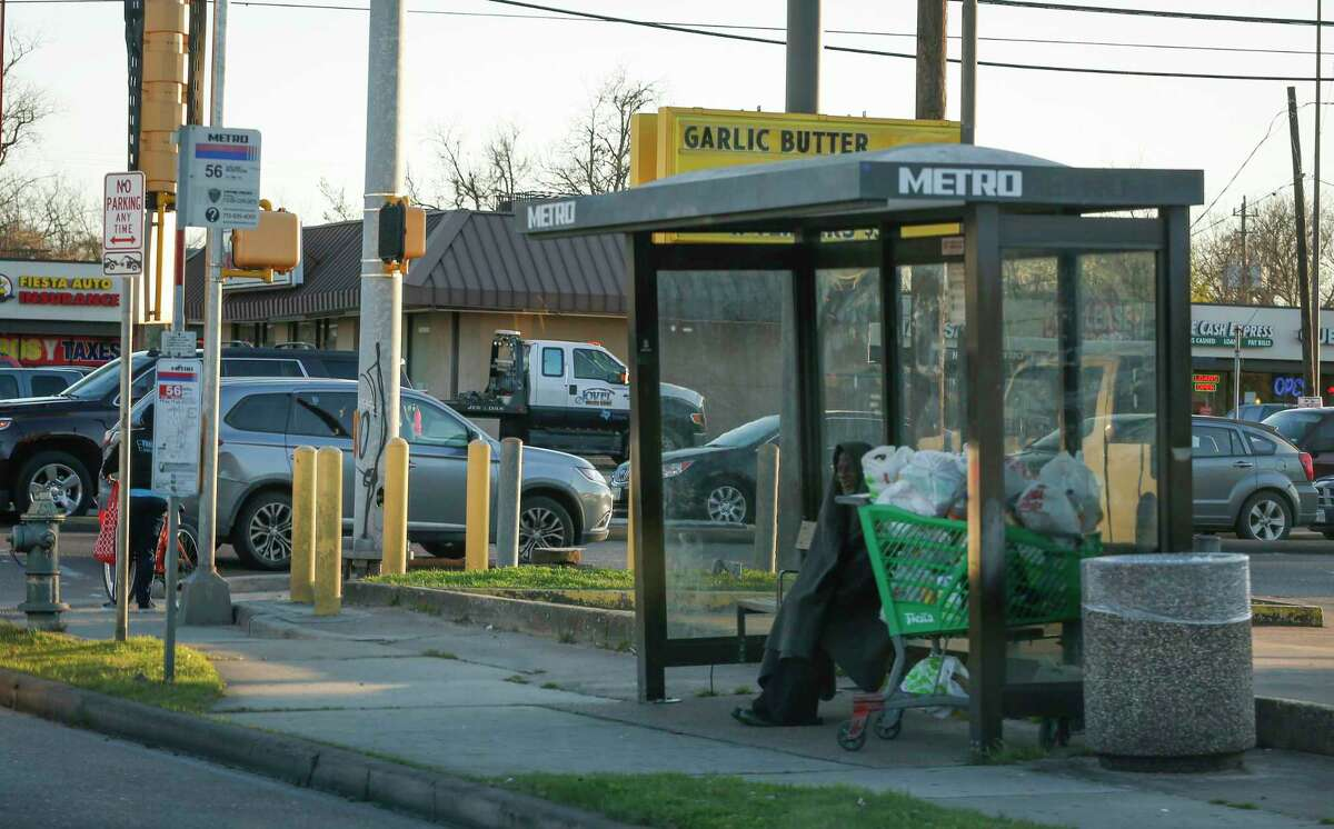 A homeless man seeks shelter in a bus stop at Tidwell and Airline on Feb. 26, 2020, in Houston. Metropolitan Transit Authority is making changes to the 54 Scott and and 56 Montrose/Airline routes as the first steps to improve 17 corridors with better bus stops, access and traffic signal timing.