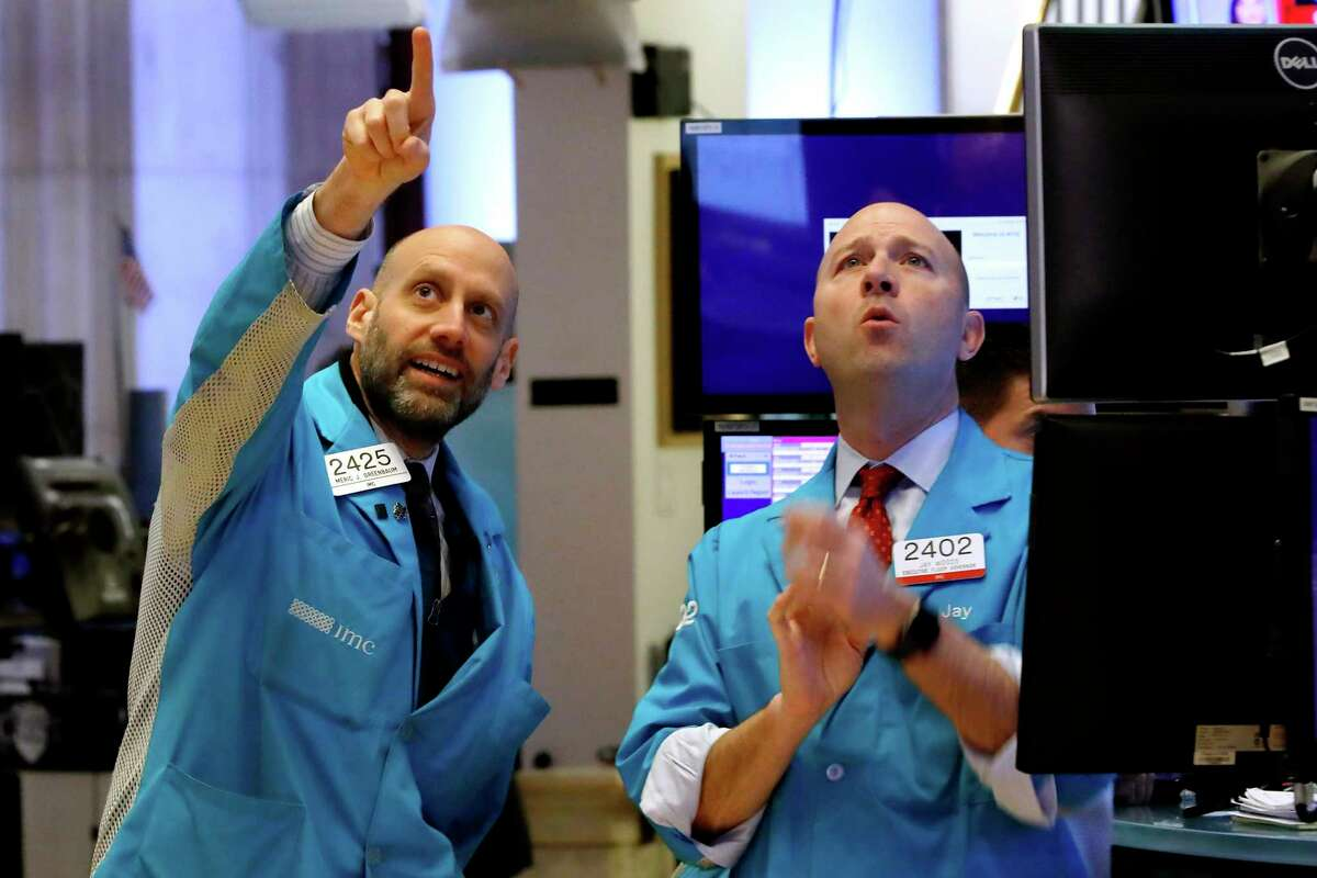Specialists Meric Greenbaum, left, and Jay Woods work on the floor of the New York Stock Exchange, Friday, Feb. 28, 2020. Stocks are opening sharply lower on Wall Street, putting the market on track for its worst week since October 2008 during the global financial crisis. (AP Photo/Richard Drew)
