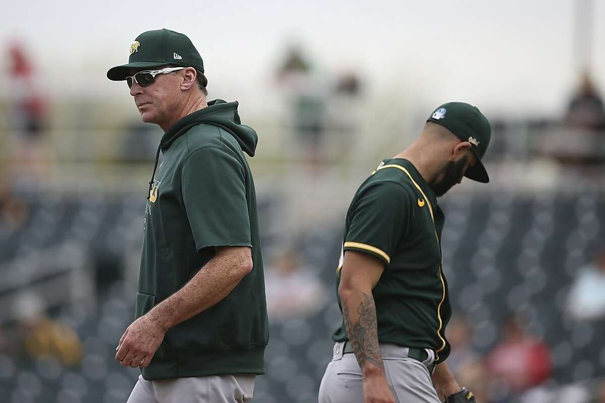 Oakland Athletics manager Bob Melvin, left, removes pitcher Mike Fiers, right, during the third inning of a spring training baseball game against the Cincinnati Reds, Friday, Feb. 28, 2020, in Goodyear, Ariz. (AP Photo/Ross D. Franklin)