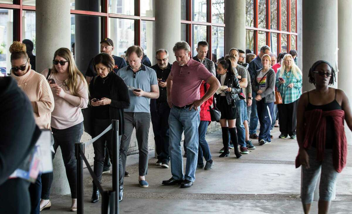 Voters line up outside the polling place in the Metropolitan Multi-Service Center to vote on the final day of early voting before the Super Tuesday primary election Friday, Feb. 28, 2020, in Houston.