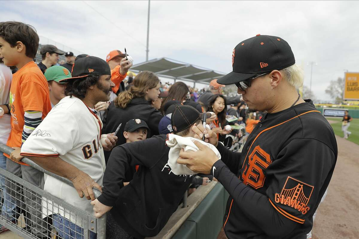San Francisco Giants' Wilmer Flores signs an autograph before a spring training baseball game against the Oakland Athletics, Sunday, Feb. 23, 2020, in Mesa, Ariz. (AP Photo/Darron Cummings)