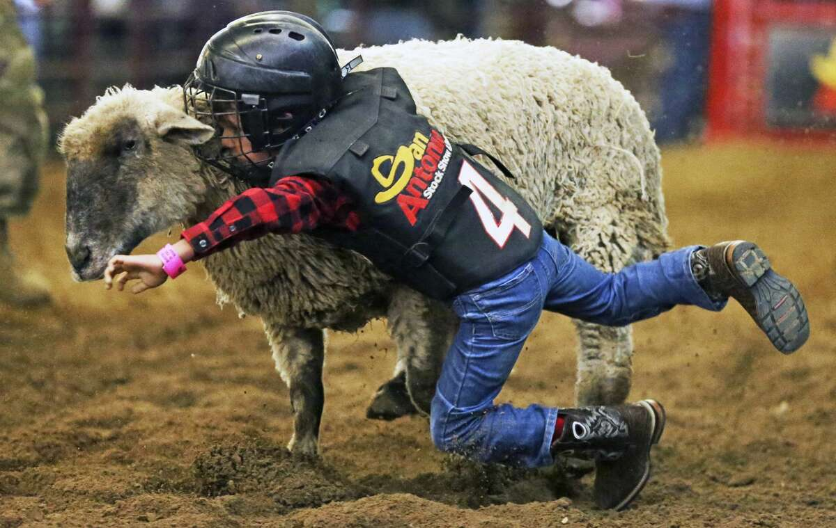 Andrew Harvey clings to his ride even after slipping off during Bustin in the Barn at the San Antonio Stock Show and Rodeo on Feb. 17, 2020.