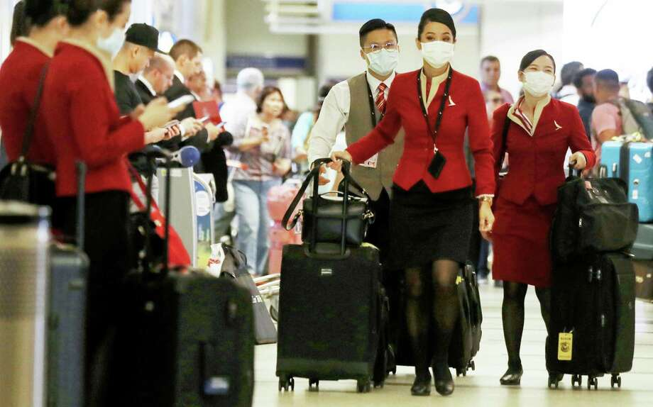 LOS ANGELES, CALIFORNIA - FEBRUARY 28: A flight crew from Cathay Pacific Airways, wearing protective masks, walk in the international terminal after arriving on a flight from Hong Kong at Los Angeles International Airport (LAX) on February 28, 2020 in Los Angeles, California. The World Health Organization (WHO) has raised the global coronavirus risk level to 'very high'. (Photo by Mario Tama/Getty Images) Photo: Mario Tama, Staff / Getty Images / 2020 Getty Images