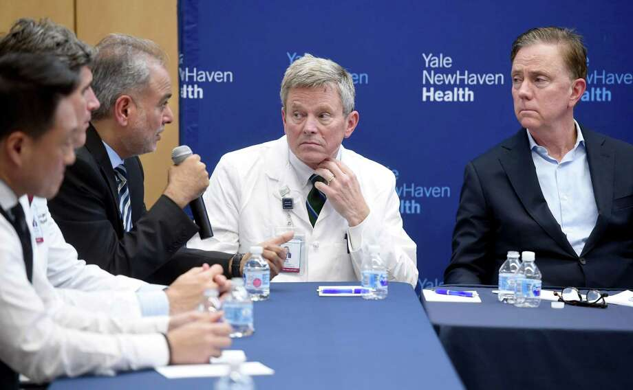 Dr. Michael Ivy (center), Deputy Chief Officer of Yale New Haven Health System, and Governor Ned Lamont (right) listen to State Senator Saud Anwar (left) speak at a roundtable discussion on the impact of the coronavirus at Bridgeport Hospital's Milford Campus on February 28, 2020. Photo: Arnold Gold / Hearst Connecticut Media / New Haven Register