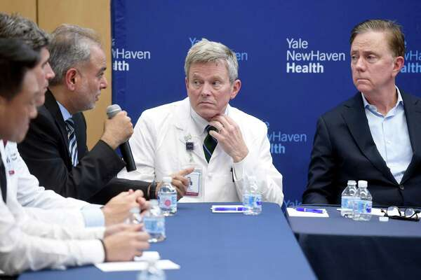 Dr. Michael Ivy (center), Deputy Chief Officer of Yale New Haven Health System, and Governor Ned Lamont (right) listen to State Senator Saud Anwar (left) speak at a roundtable discussion on the impact of the coronavirus at Bridgeport Hospital's Milford Campus on February 28, 2020.