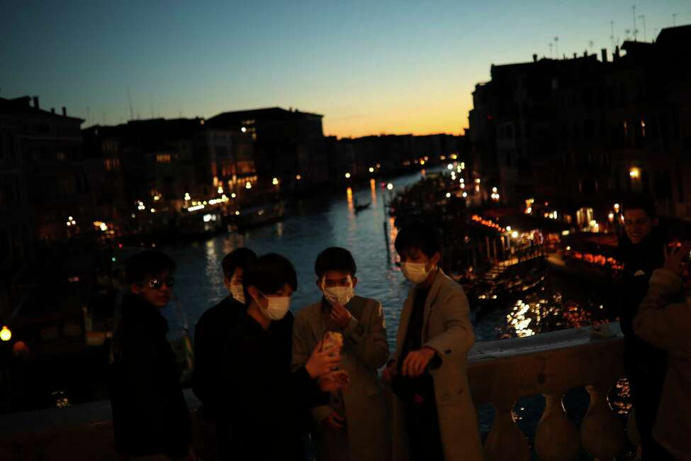 Tourists wearing protective masks pose for a photograph at the Rialto bridge as the sun sets in Venice, Italy, Friday, Feb. 28, 2020. Authorities in Italy decided to re-open schools and museums in some of the areas less hard-hit by the coronavirus outbreak in the country which has the most cases outside of Asia, as Italians on Friday yearned for a return to normal life even amid fears that the outbreak could plunge the country's economy into recession. (AP Photo/Francisco Seco)