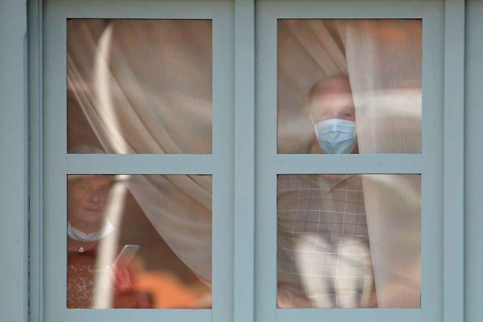 People wearing face masks look through a window of the H10 Costa Adeje Palace hotel in La Caleta, in the Canary Island of Tenerife, Spain, Friday Feb. 28, 2020. Some guests have started to leave the locked down hotel after undergoing screening for the new virus that is infecting hundreds worldwide. (AP Photo/Joan Mateu)