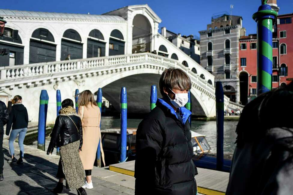 A man wearing a protective mask walks past the Ponte di Rialto (Rialto Bridge) in Venice, Italy, Friday, Feb. 28, 2020. Authorities in Italy decided to re-open schools and museums in some of the areas less hard-hit by the coronavirus outbreak in the country which has the most cases outside of Asia, as Italians on Friday yearned for a return to normal life even amid fears that the outbreak could plunge the country's economy into recession. (Claudio Furlan/Lapresse via AP)