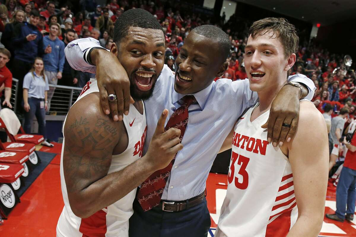 Dayton coach Anthony Grant, center, gives a hug to players Trey Landers, left, and Ryan Mikesell following the team's 82-67 win over Davidson in an NCAA college basketball game Friday, Feb. 28, 2020, in Dayton, Ohio. (AP Photo/Gary Landers)
