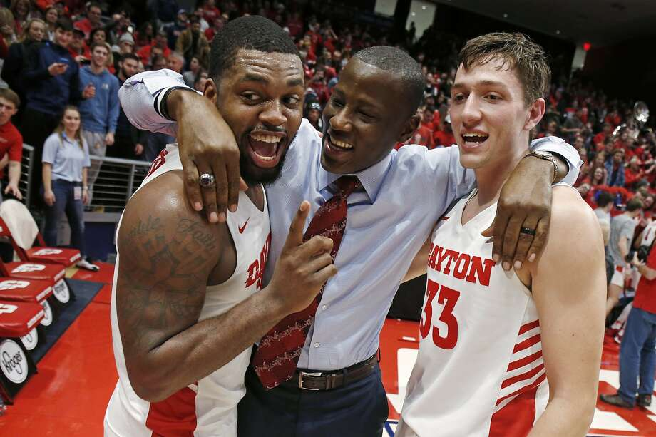 Dayton coach Anthony Grant (center) hugs Trey Landers (left) and Ryan Mikesell after clinching the Atlantic 10 title Friday. Photo: Gary Landers / Associated Press