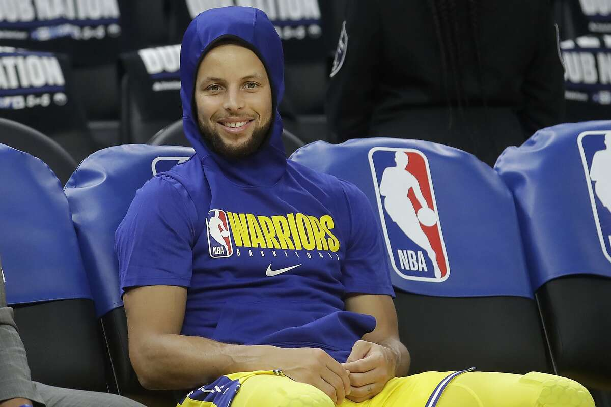 Golden State Warriors guard Stephen Curry smiles on the bench as players warm up before an NBA basketball game between the Warriors and the Los Angeles Lakers in San Francisco, Thursday, Feb. 27, 2020. Curry wrote an essay for Time where he discussed being tested for the coronavirus.