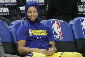 Golden State Warriors guard Stephen Curry smiles on the bench as players warm up before an NBA basketball game between the Warriors and the Los Angeles Lakers in San Francisco, Thursday, Feb. 27, 2020. (AP Photo/Jeff Chiu)