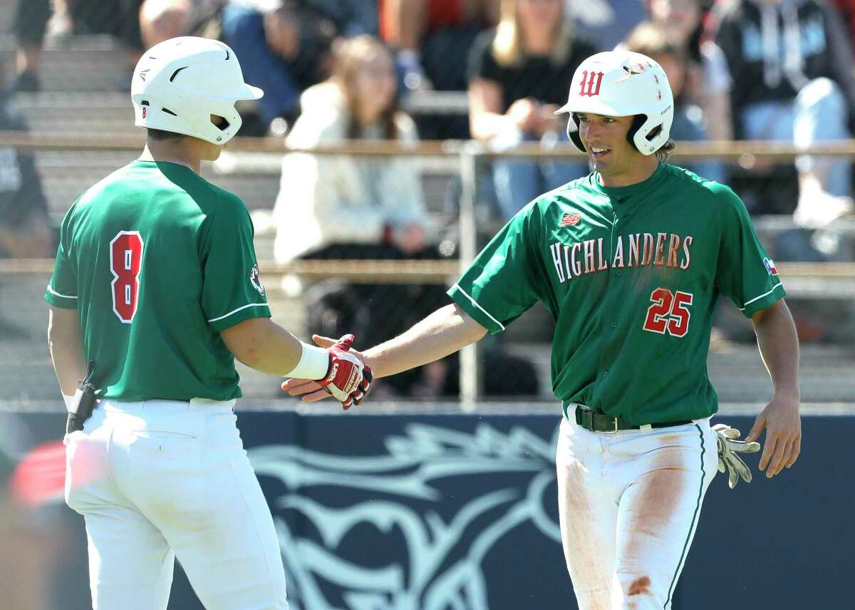 Matthew Bulovas #25 of The Woodlands gets a high-five from Drew Romo after scoring the go-head run off Will Thomas's double during the sixth inning of a non-district high school baseball game at Kingwood High School, Friday, Feb. 28, 2020, in Kingwood.