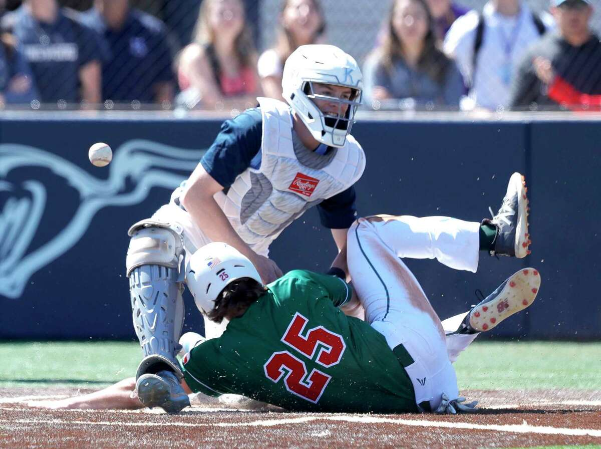 Matthew Bulovas #25 of The Woodlands collides with Kingwood catcher Justin Long (9) at the plate to score the go-head run off Will Thomas's double during the sixth inning of a non-district high school baseball game at Kingwood High School, Friday, Feb. 28, 2020, in Kingwood.
