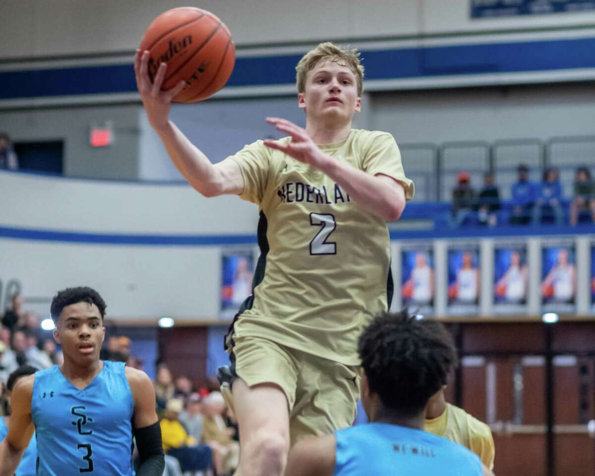Hayden Hefner (2) puts up an inside shot over traffic in the second half as the Nederland Bulldogs fell to the Sharks of Shadow Creek in the area round playoffs at Barbers Hill High School on Friday, February 28, 2020. Fran Ruchalski/The Enterprise