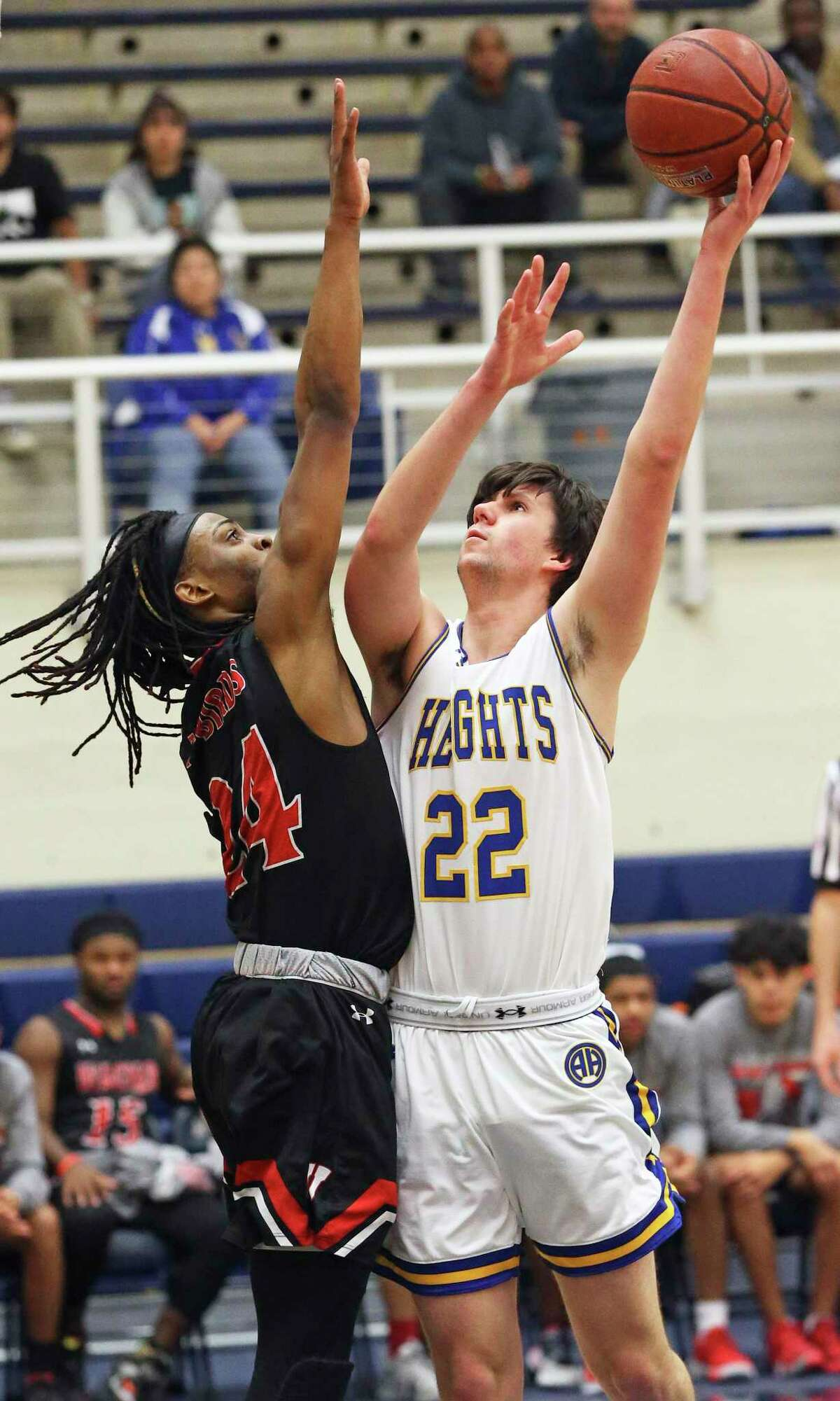 Mules forward Westin Voss stretches for a shot against Journee Phillips as Wagner plays Alamo Heights in boys basketball playoff action at Taylor Field House on Feb. 28, 2020.