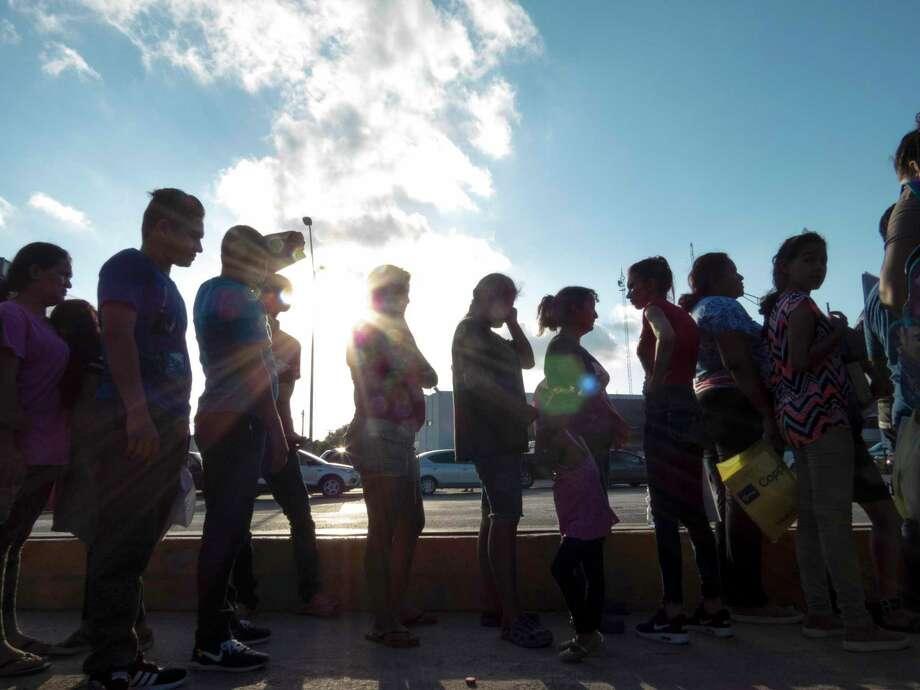 En esta fotografía de archivo del 5 de octubre de 2019, varios migrantes que desean asilo en Estados Unidos hacen fila con sus documentos en el campo para migrantes afuera de El Puente Nuevo, en Matamoros, México. Photo: Denise Cathey /Associated Press / 2019 The Brownsville Herald