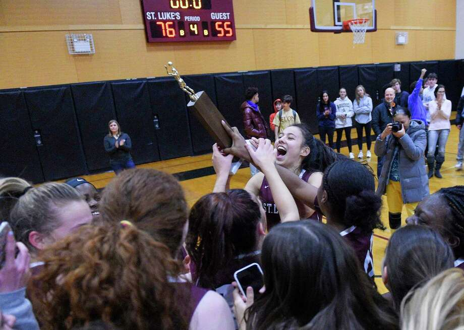 St. Luke's Caroline Lau celebrates with the trophy following the Storm's 76-55 win against Green Farms Academy in the FAA girls basketball final in New Canaan, on Friday. Photo: Matthew Brown / Hearst Connecticut Media / Stamford Advocate
