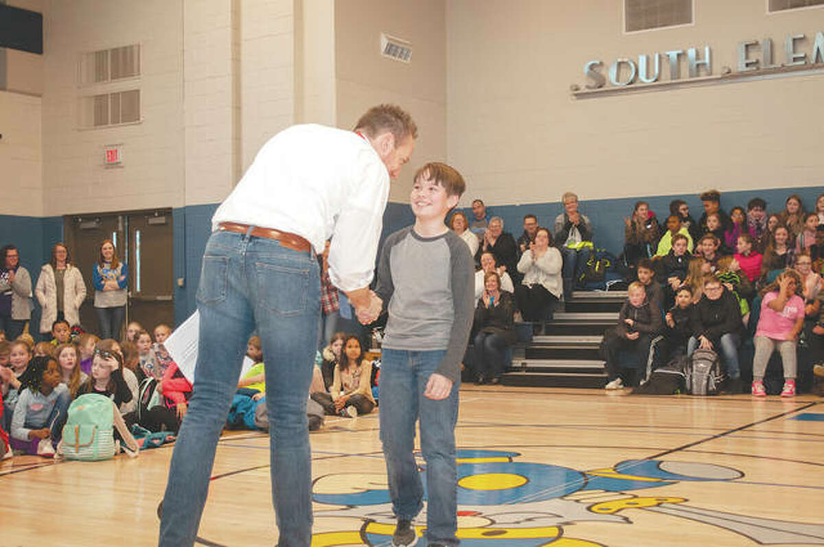 South Jacksonville Elementary School Principal Tim Chipman congratulates fifth-grader Kellon Oldenettel on his receiving a national award. Oldenettel was given a silver medallion from the Prudential Spirit of Community Awards.