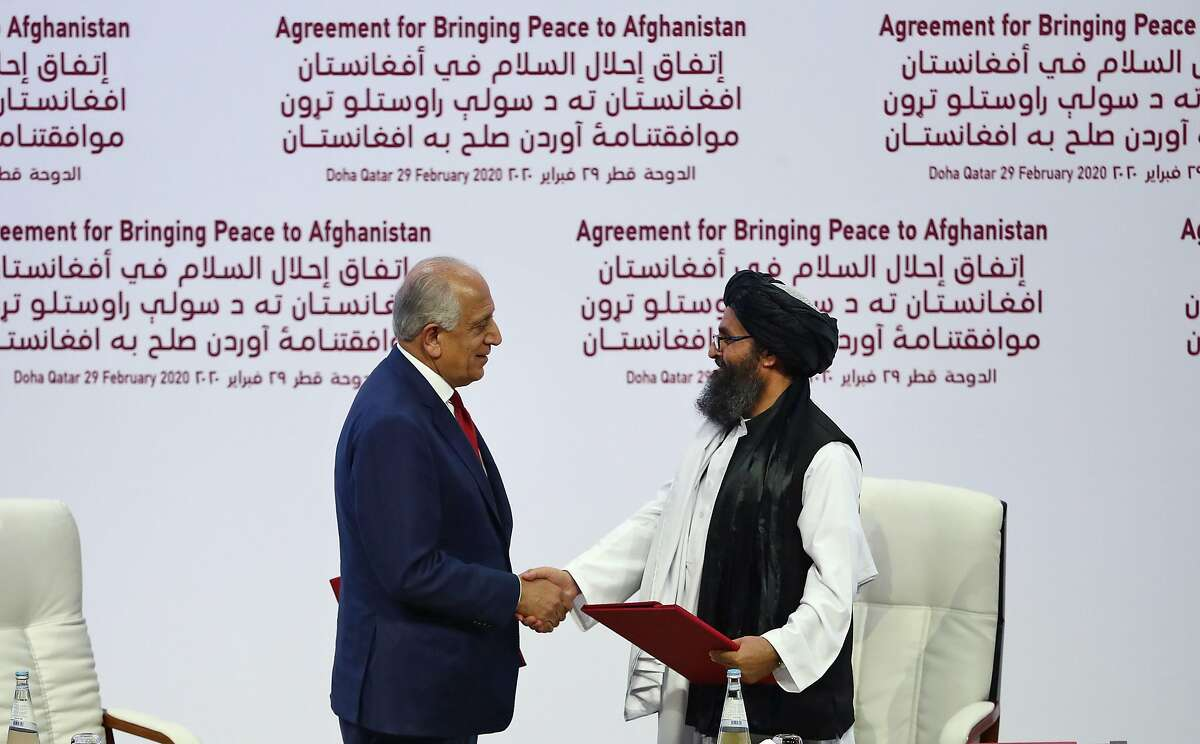 (L to R) US Special Representative for Afghanistan Reconciliation Zalmay Khalilzad and Taliban co-founder Mullah Abdul Ghani Baradar shake hands after signing a peace agreement during a ceremony in the Qatari capital Doha on February 29, 2020. - The United States signed a landmark deal with the Taliban, laying out a timetable for a full troop withdrawal from Afghanistan within 14 months as it seeks an exit from its longest-ever war. Pompeo called on the Taliban to honour its commitments to sever ties with jihadist groups as Washington signed a landmark deal with the Afghan insurgents. (Photo by KARIM JAAFAR / AFP) (Photo by KARIM JAAFAR/AFP via Getty Images)