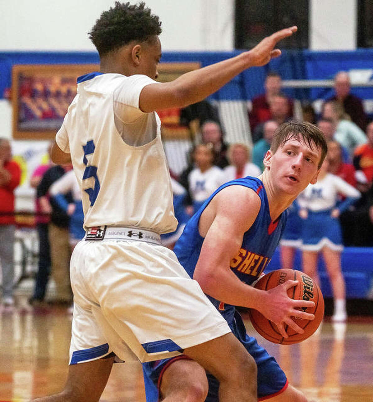 Roxana's Andrew Beckman (right) looks to pass out of pressure from Marquette Catholic's Cortez Harris during the championship game of the Roxana Class 2A Regional on Friday night at Milazzo Gym in Roxana.