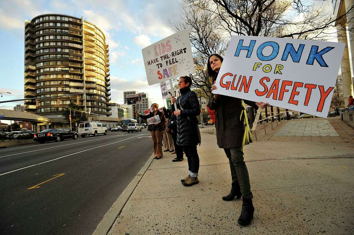 Members of the Enough Campaign Wendy Skratt, right, and Laurie Doig hold signs along Washington Boulevard during a protest in support for reasonable gun safety laws in front of the Stamford Government Center in Stamford, Conn., on Thursday, Oct. 30, 2014.
