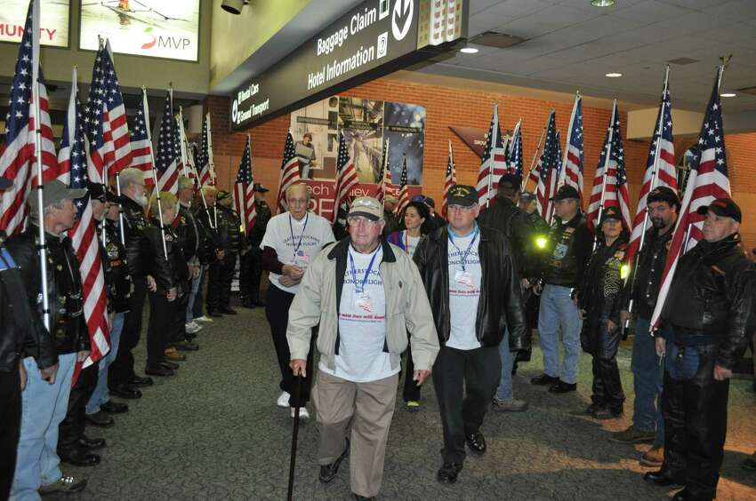 Neil Taber, 88, Altamont, N.Y. (center) at passes through the Patriot Riders honor guard Saturday, Nov. 8, 2014, on his way to board the Leatherstocking Honor Flight. Tabor served with the Army Air Corps during World War II. (Doug Myers/Albany International Airport)