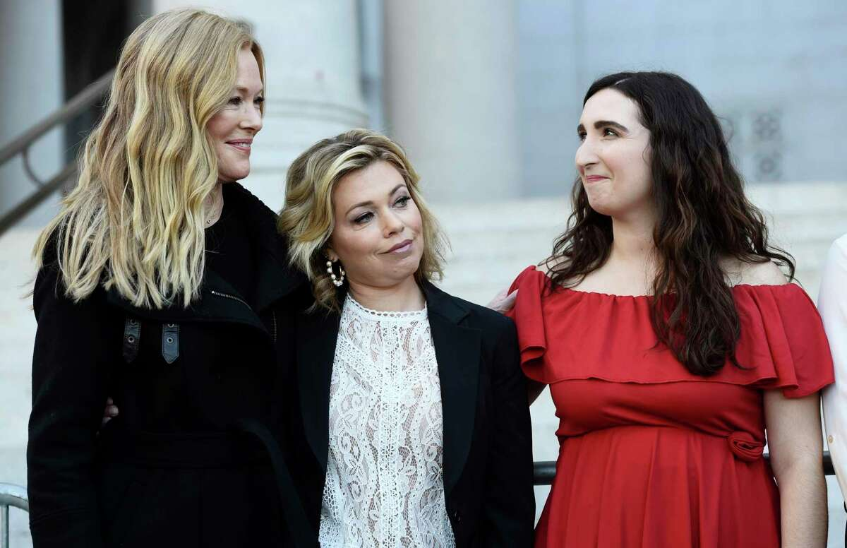 Actresses Caitlin Dulany, left, Lauren Sivan, center, and Sarah Ann Masse stand together at a news conference by the