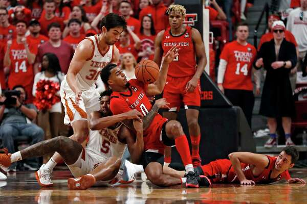 Texas' Royce Hamm Jr. (5) and Texas Tech's Kyler Edwards (0) fight for control of the ball during the second half of an NCAA college basketball game Saturday, Feb. 29, 2020, in Lubbock, Texas. (AP Photo/Brad Tollefson)