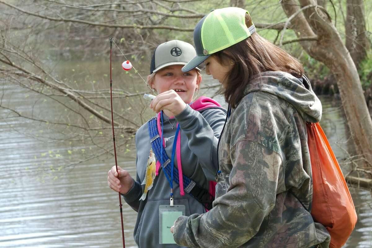 """Nora Regan shows off her catch to friend Elena Davis as they learn about fishing during the """"Becoming an Outdoors Girl"""" event at University of Houston - Clear Lake Saturday, Feb. 29."""