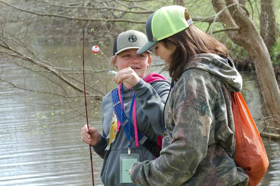 "Nora Regan shows off her catch to friend Elena Davis as they learn about fishing during the ""Becoming an Outdoors Girl"" event at University of Houston - Clear Lake Saturday, Feb. 29. Photo: Kirk Sides/Staff Photographer"