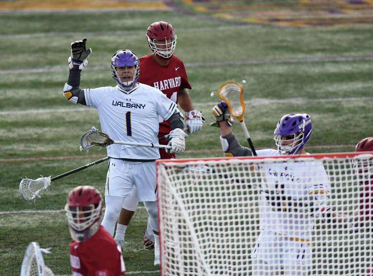 University at Albany's Tehoka Nanticoke (1) and Corey Yunker (11) celebrate a goal against Harvard during an NCAA lacrosse game Saturday, Feb. 29, 2020, in Albany, N.Y.,