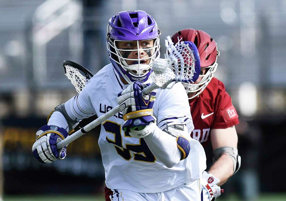 University at Albany's Ron John (33) moves the ball against Harvard during an NCAA lacrosse game Saturday, Feb. 29, 2020, in Albany, N.Y.,