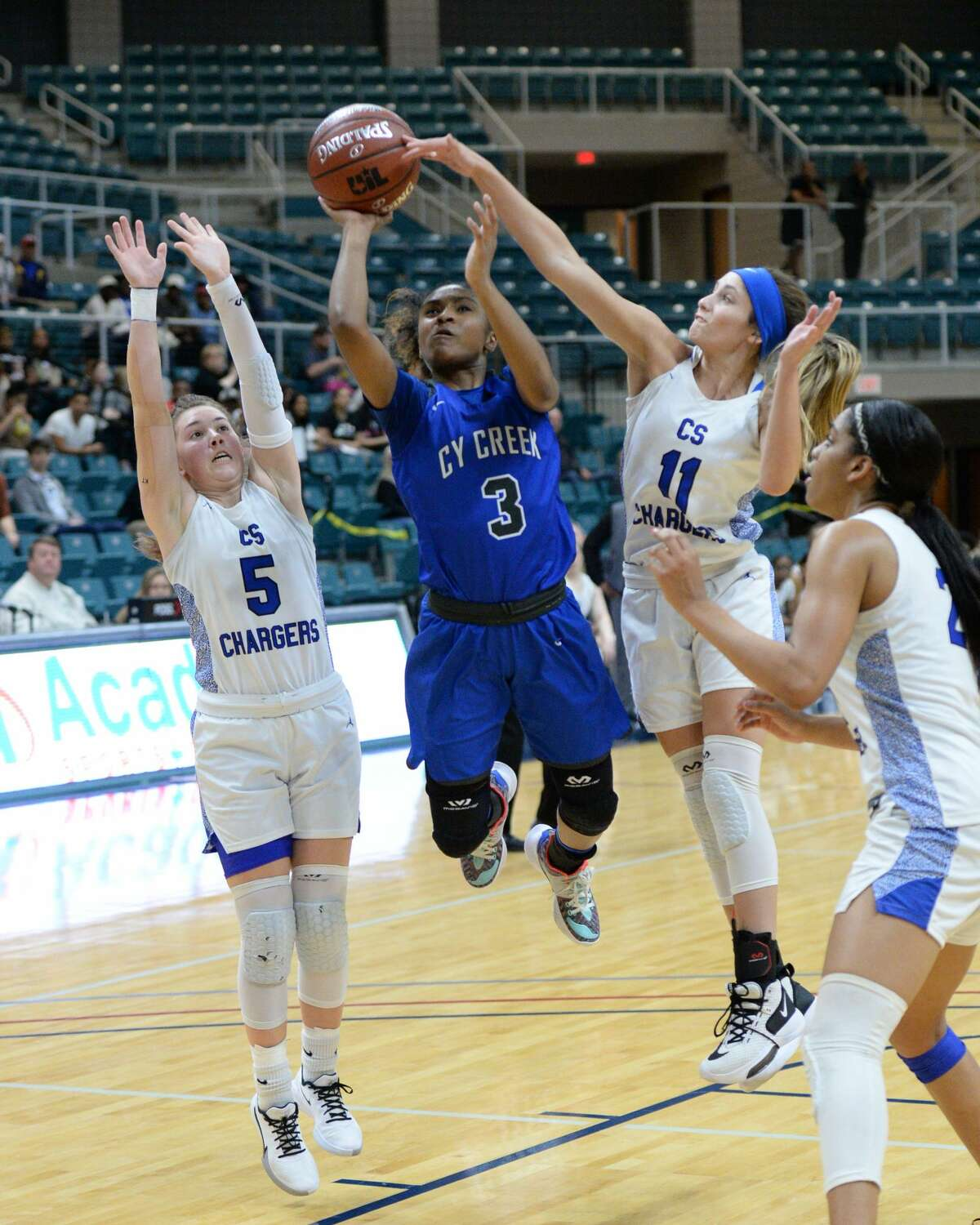 Rori Harmon (3) of Cy Creek drives to the basket between Kylie Minter (5) and Kylenn Tolopka (11) of Clear Springs during the third quarter of a Girls Region III-6A championship between the Cy Creek Cougars and the Clear Springs Chargers on Saturday, February 29, 2020 at the Leonard Merrell Center, Katy, TX.
