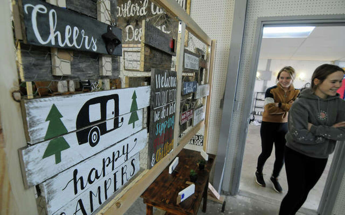 Shoppers pass by wooden handmade signs Saturday during the grand opening of The Hangar Emporium, 423 N. Bellwood Drive, in East Alton.