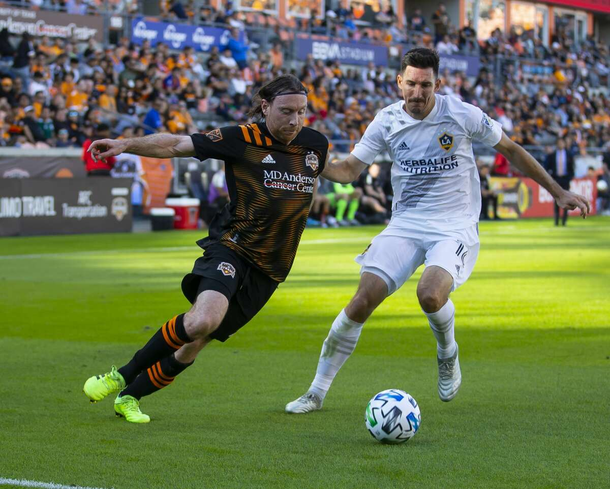 Houston Dynamo midfielder Tommy McNamara brings the ball downfield past Los Angeles Galaxy midfielder Sacha Kljestan during a match between the Houston Dynamo and LA Galaxy, Saturday, Feb. 29, 2020, at BBVA Stadium in Houston.