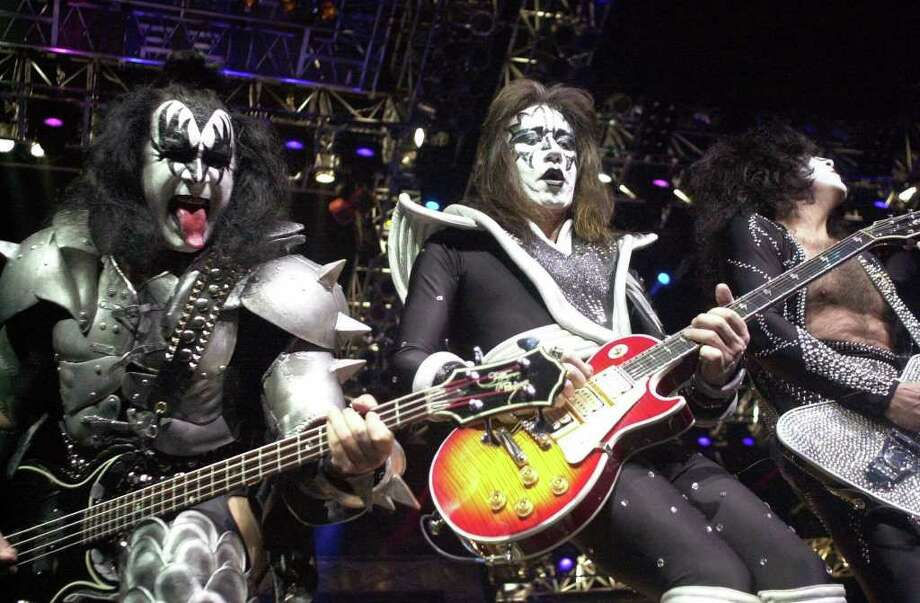 Kiss guitarist Paul Stanley, right, waves to the crowd as guitarist Ace Frehley, center, and bassist Gene Simmons, left, play during the band's farewell concert in the Detroit area in this May 25, 2000 file photo at the Palace of Auburn Hills, Mich. (AP Photo/Paul Warner, File) Photo: PAUL WARNER / AP