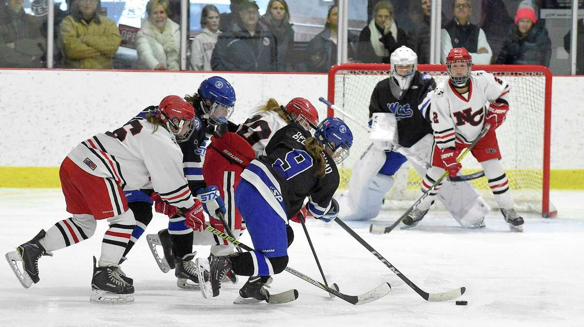 Darien Kate Bellissimo (9) battles against New Canaan in the second period of the FCIAC Girls' Ice Hockey finals on Saturday.