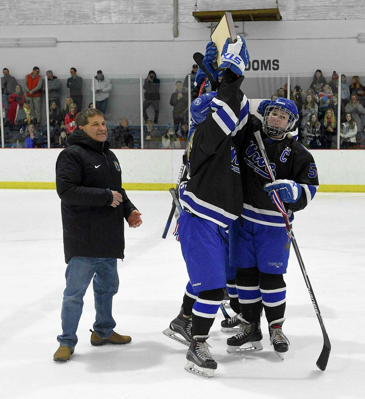 Darien team captains celebrate after accepting the championship plaque after defeating New Canaan 4-2 in the FCIAC Girls' Ice Hockey finals at the Darien Ice House in Darien, Conn., Saturday, Feb. 29, 2020.