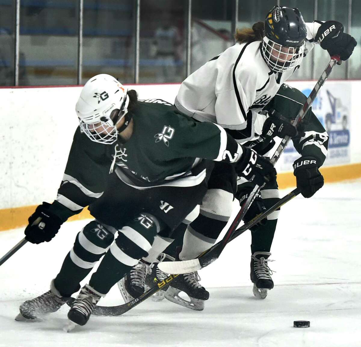 West Haven, Connecticut - February 29, 2020: Tess Csejka of Amity/New Haven/ Cheshire Blades, center, tries to split Olivia Gill of Guilford,left, and teammate Megan Fernandes, right, as she chases the puck the during first period of the SCC 2020 Girls Ice Hockey Championship Saturday afternoon at Bennett Rink in West Haven.