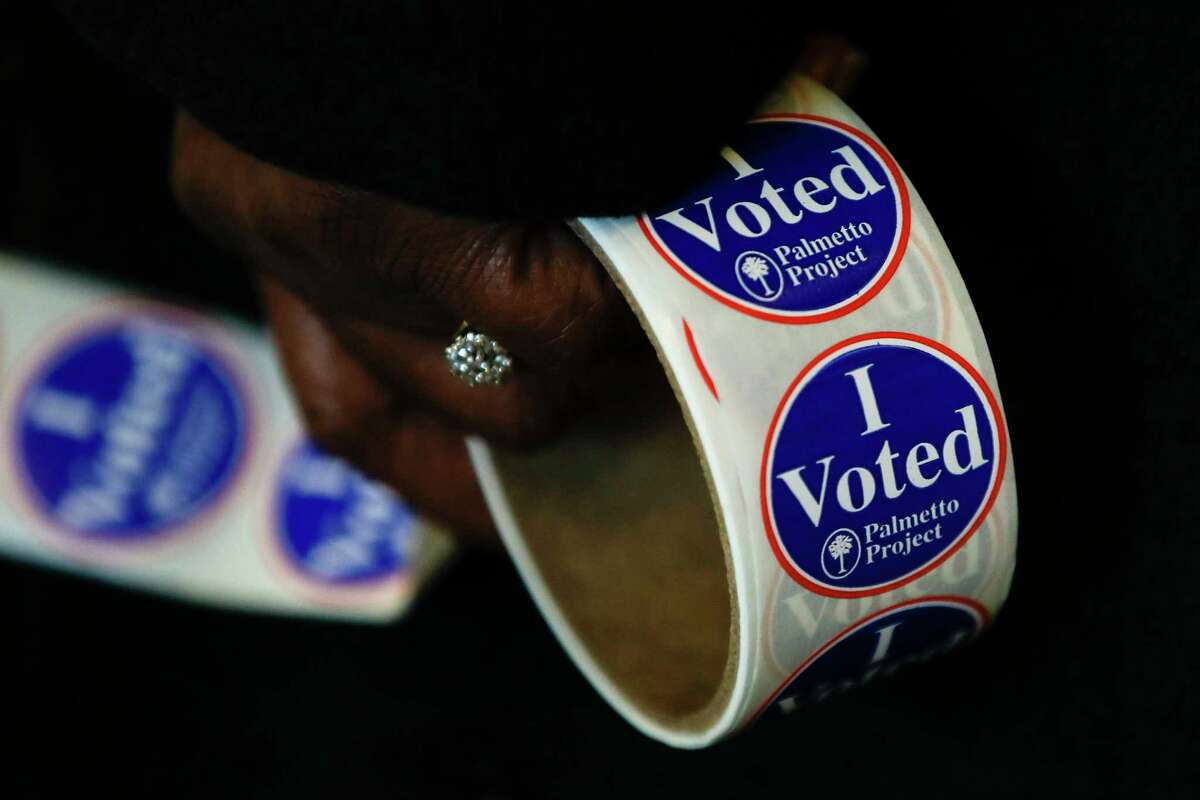 A worker holds stickers at a polling place for the South Carolina primary election, Saturday, Feb. 29, 2020, in Columbia, S.C. (AP Photo/Matt Rourke)