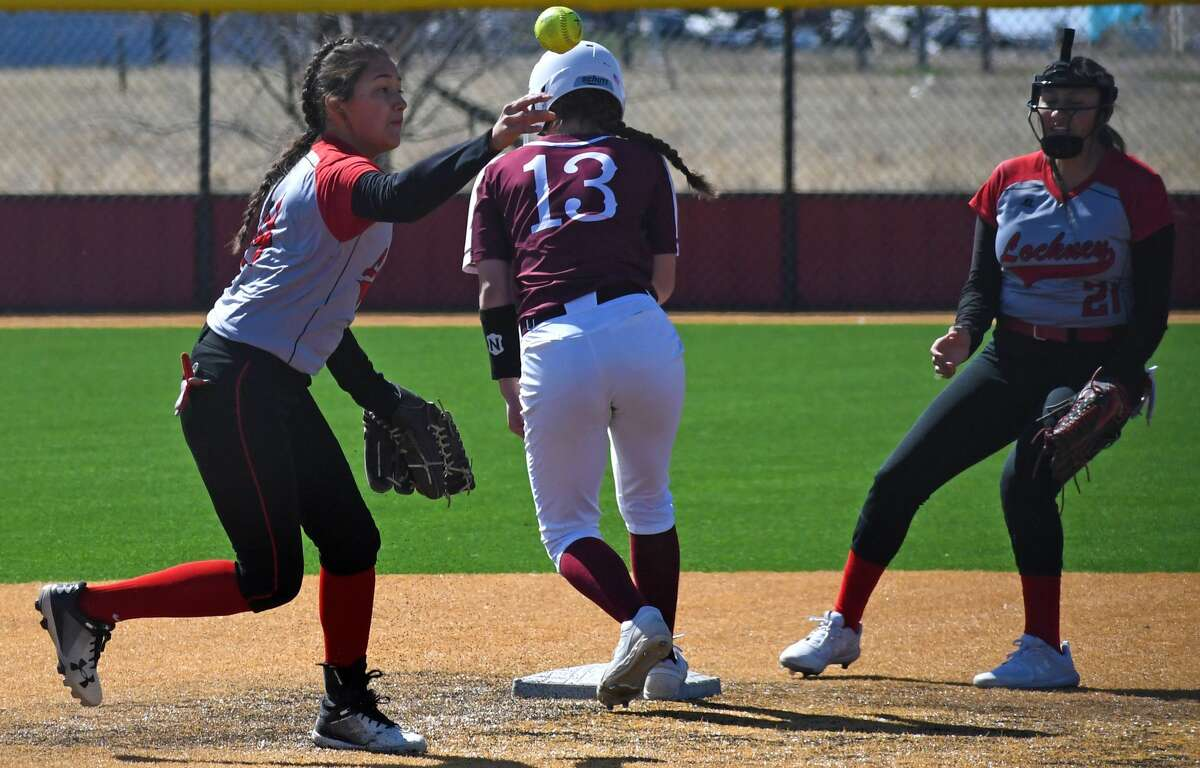 Lockney's Yanellie Bernal (left) tosses the ball over to first base for the out in front of Tulia base runner Allie Ramirez during their high school softball game as part of the Jesse L. Garza Lady Horn Softball Tournament on Friday, Feb. 28, 2020. Looking on is Lockney's Gabriella Cervantes