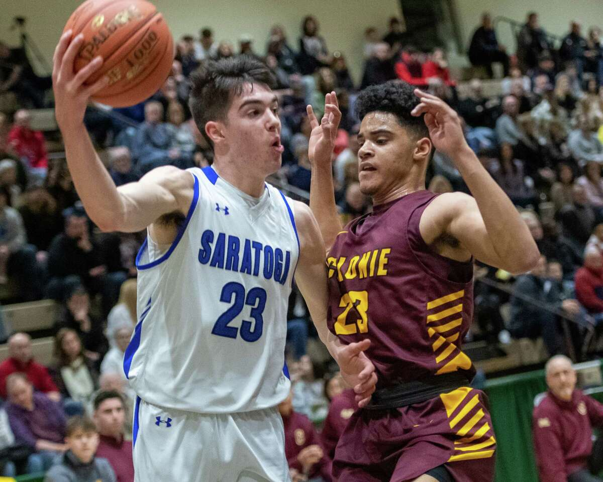 Saratoga junior Matt Rogan drives by Colonie junior Marcus Shelton during the Section II, Class AA quarterfinals at Hudson Valley Community College in Troy, NY on Saturday, Feb. 29, 2020 (Jim Franco/Special to the Times Union.)