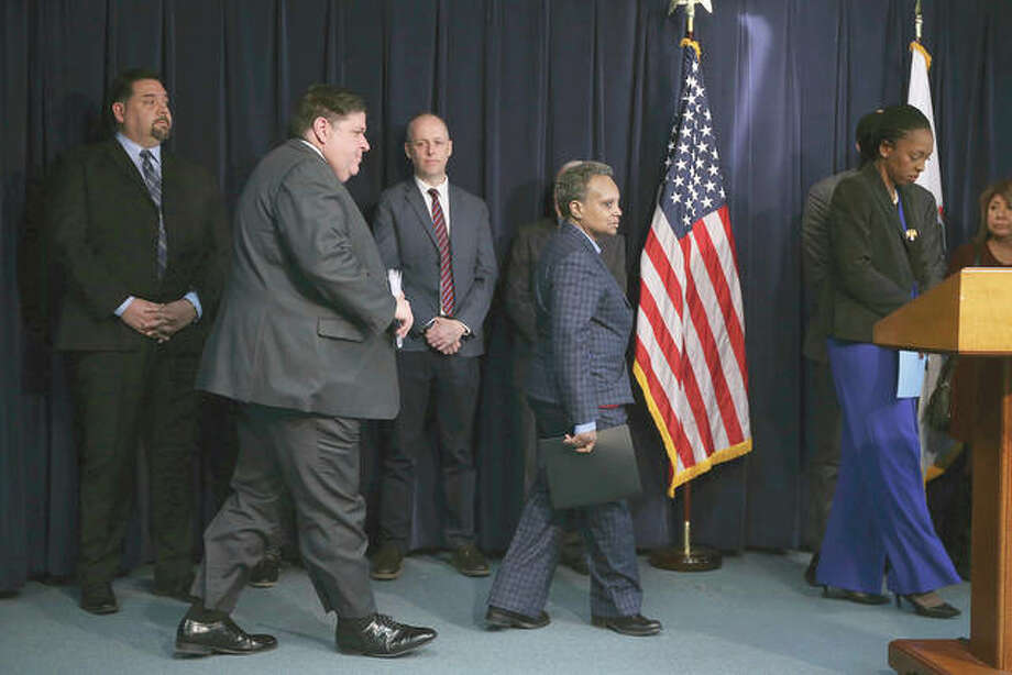 Gov. J.B. Pritzker, along with Chicago Mayor Lori Lightfoot and public health officials, arrive to provide updated guidance around the coronavirus during a news conference Friday in Chicago.= Photo: Antonio Perez | Chicago Tribune (AP)