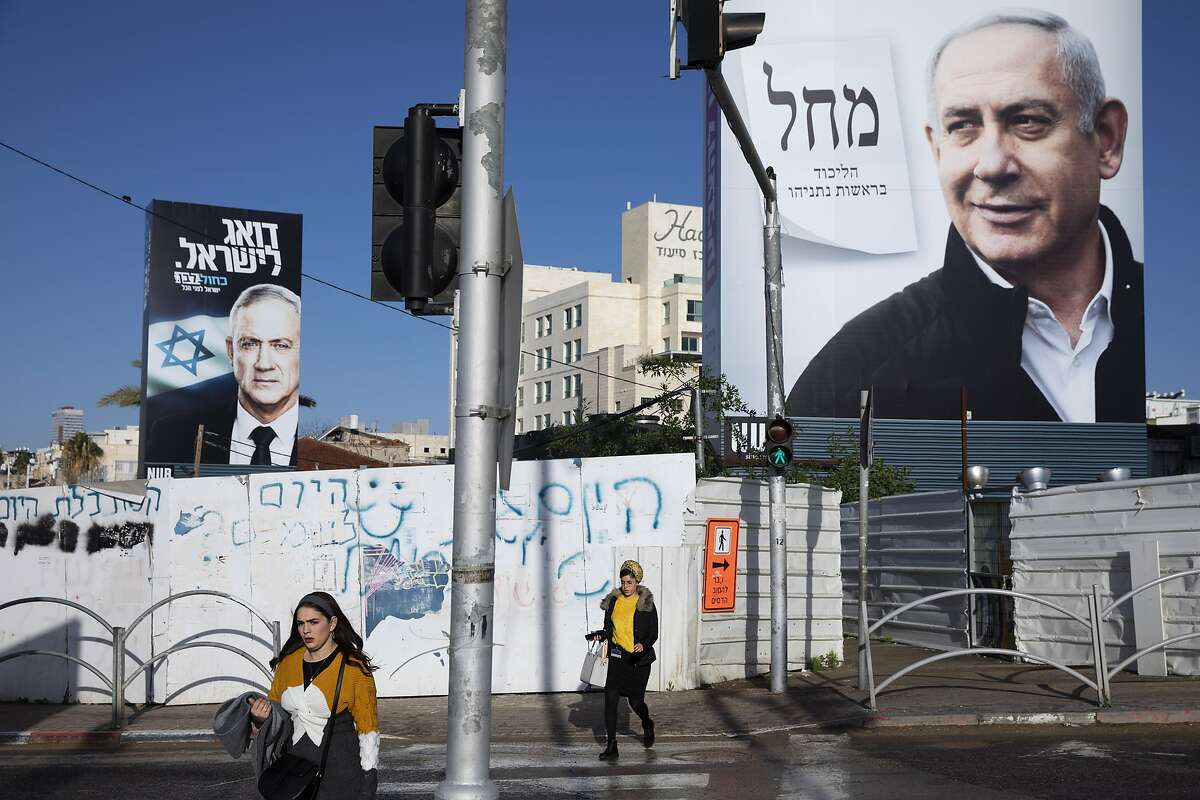 People walk next to election campaign billboards for Likud Party, shows Israeli Prime Minister Benjamin Netanyahu, right, and the Blue and White party, the opposition party led by Benny Gantz, left, in Bnei Brak, Israel, Sunday, March. 1, 2020. Israel heads into its third election in less than a year on Monday, March 2nd. (AP Photo/Oded Balilty)