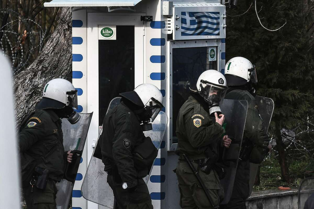 Greek riot police officers stand at a border checkpoint during clashes with migrants trying to cross along the Greece-Turkey border in the village of Kastanies on March 1, 2020. - Thousands more migrants reached the Turkish border with Greece on March 1, 2020, AFP journalists said, after the Turkish President threatened to let them cross into Europe. At least 2,000 people including women and children arrived on the morning from Istanbul and walked through a field towards the Pazarkule border gate, a correspondent said. The group included Afghans, Syrians and Iraqis. (Photo by Sakis MITROLIDIS / AFP) (Photo by SAKIS MITROLIDIS/AFP via Getty Images)