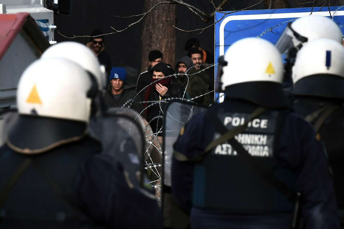 Greek riot police officers watch migrants trying to cross along the Greece-Turkey border neat the village of Kastanies on March 1, 2020. - Thousands more migrants reached the Turkish border with Greece on March 1, 2020, AFP journalists said, after the Turkish President threatened to let them cross into Europe. At least 2,000 people including women and children arrived on the morning from Istanbul and walked through a field towards the Pazarkule border gate, a correspondent said. The group included Afghans, Syrians and Iraqis. (Photo by Sakis MITROLIDIS / AFP) (Photo by SAKIS MITROLIDIS/AFP via Getty Images)