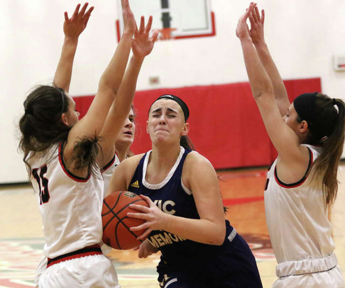 CM's Anna Hall (middle) drives to the basket through a triple-team from Highland's Megan Kronk (left), Bella LaPorta and Ellie Brown (right) on Thursday in the title game of the Effingham Class 3A Sectional. Hall finishes her career with 1,700 points to rank No. 3 all-time at CM.