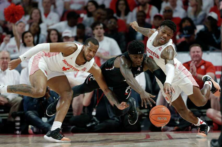 Cincinnati forward Tre Scott, center, Houston forward Justin Gorham, left, and guard Marcus Sasser, right, chase loose ball during the first half of an NCAA college basketball game, Sunday, March 1, 2020, in Houston.